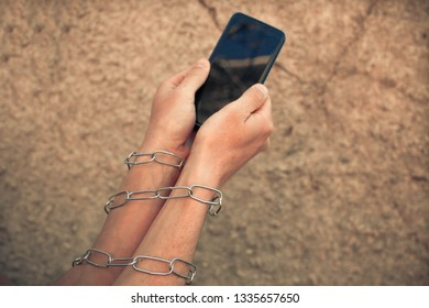 Hands close up hold phone held down by a chain