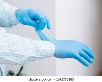 Hands close up putting a blue latex glove on