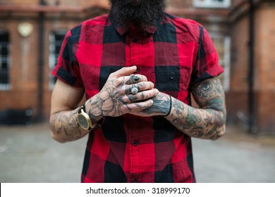 Hands close up of young tattooed man portrait in Shoreditch borough, London. Hipster style.