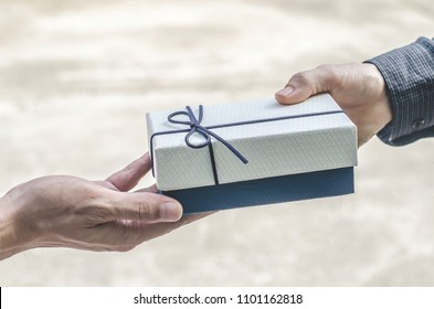 From hands to hands. Close-up of hands holding gift box giving and receiving a present.