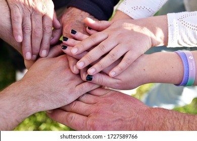 Hands close-up of people of various ages symbolising the concept of family, love and different generations of society working together as a team.
