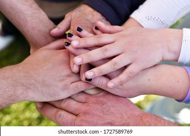 Hände Nahaufnahmen von Menschen verschiedener Altersgruppen symbolisieren das Konzept der Familie, der Liebe und verschiedener Generationen der Gesellschaft, die als Team zusammenarbeiten.