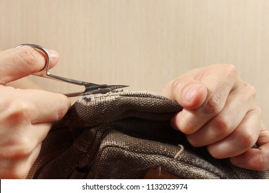 Hands of clothier with a pair of scissors cut a strong cloth close up