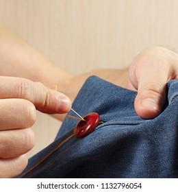 Hands of clothier sew a button to a denim fabric close up