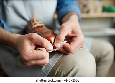 Hands of cobbler stretching brown leather on boot model in workshop
