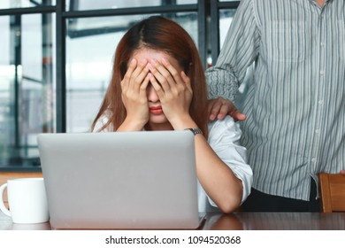 Hand's of colleague comforting depressed sad Asian woman with hands on face crying on the workplace in office.