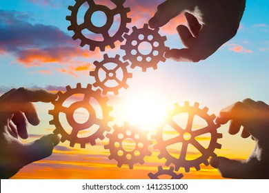 Hands collect gear in a puzzle against the sky in the sunset. Business concept idea, partnership, innovation, teamwork, cooperation