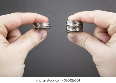 Hands compare two piles of coins of different sizes, indicating the return on investment.