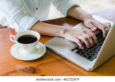 Hands, computer and coffee on wooden table