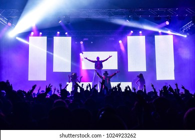 Hands up at a concert. Silhouettes of people on dancefloor. White ledwall ideal for inserting text or logos. Male and female animation. man on stilts. All with arms up