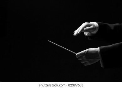 Hands of a conductor isolated on black background, black and white