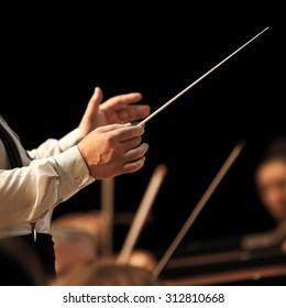 The hands of the conductor on the background of the orchestra in dark colors