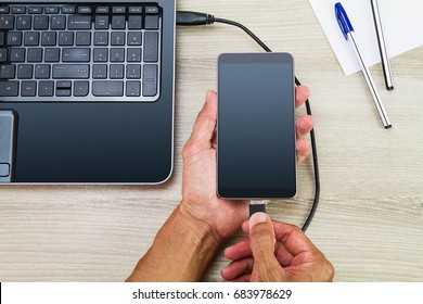Hands connecting smartphone to laptop by using usb cable on wooden desk with pen and paper, business concept