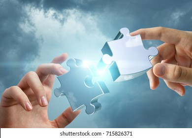 Hands connects two of the puzzle in the sky. The concept of business strategy.