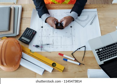 Hands of construction engineer with smartphone working at table with blueprint of building