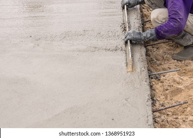 Hands of construction worker screed plastering the cement floor
