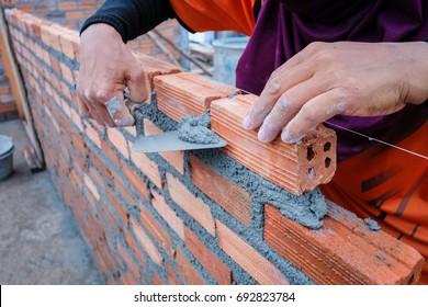 The hands of the construction workers are building a brick red brick wall