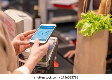 Hands of contemporary mature female customer with smartphone over payment machine standing by cashier counter in supermarket