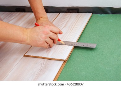 Hands of a contractor measuring the proper length of a laminate piece