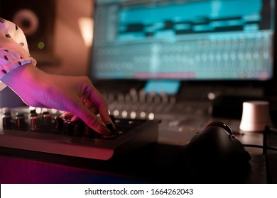 Hands controlling or mixing electronic music track.