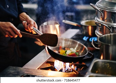 Hands of cook frying vegetables on pan