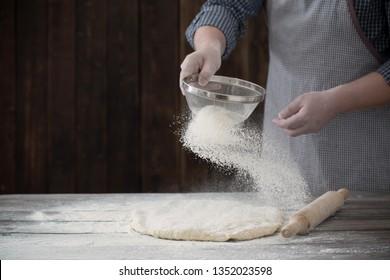 hands cooking dough on dark wooden background