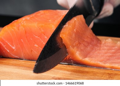 Hands cooks close-up. The chef cuts with a knife a red fish, smoked salmon on a wooden cutting board. Black wooden table on background.
