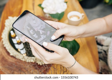 Hands of cosmetics brand owner taking photos of new products and uploading on social media or online shop