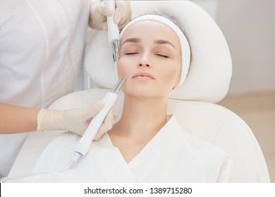 The hands of a cosmetologist do microcurrent myostimulation on the face of a girl client lying on a couch. Face lift concept and skin color restoration