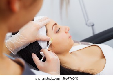 Hands of cosmetologist making injection in face, lips. Young woman gets beauty facial injections in salon. Face aging, rejuvenation and hydration procedures. Aesthetic cosmetology. Close up.