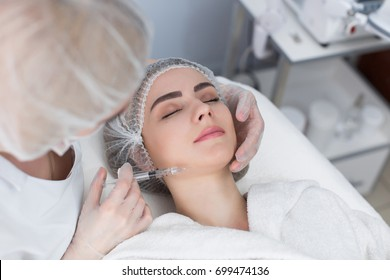 Hands of cosmetologist making injection in face, lips. Young woman gets beauty facial injections in salon. Face aging, rejuvenation and hydration procedures. Aesthetic cosmetology.