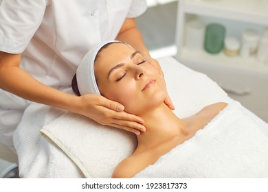 Hands of cosmetologist making manual relaxing rejuvenating facial massage for young woman in beauty salon. Rejuvenating facial massage in cosmetology