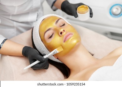 Hands of cosmetology specialist applying gold facial mask using brush, making skin hydrated and face glowing and skin. Attractive brunette relaxing with closed eyes and enjoying spa procedures.