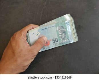 Hands is counting money (Banknote Ringgit Malaysia) RM50 after receiving a salary. Calculation to pay debts and daily expenses.
