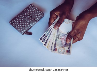 Hands counting Nigerian naira notes isolated on white background. African woman Counting or spend money. for personal finance and banking concept