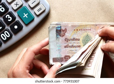 Hands counting pile of Thai Baht money and calculator on  brown paper background