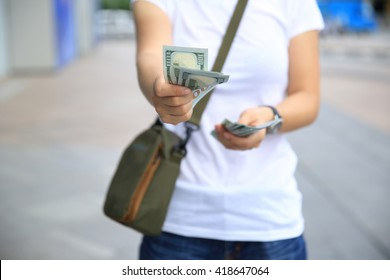 hands counting usd cash on street