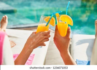 Hands of couple clinking glasses of orange juice when resting by swimming pool