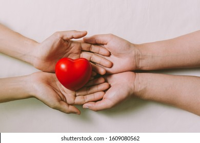 Hands couple holding red hearts, love, valentine, health care, donation and family insurance concepts, World Heart Day, prayer together.