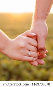Hands of a couple in love at sunset.Engagement Ring