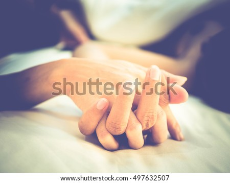 Hands of couple lovers having sex on a bed in morning with lust and love