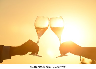 Hands of couple toasting at sunset