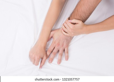 Hands of couple who having sex in bed on white crumpled sheet, focus on hands, close up. Man grasping woman. Adult, sex, love, relationship, intimate life and getero concept.
