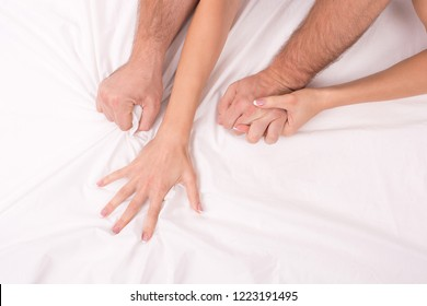 Hands of couple who making love in bed on white crumpled sheet, focus on hands, close up. Man grasping woman.