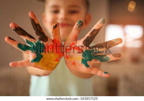Hands covered in tempura paint. Focus is on hands.