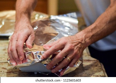 Hands covering casserole dish with aluminum foil to back in oven