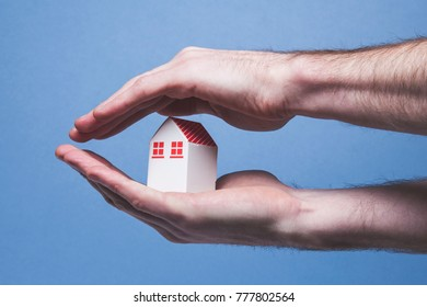 Hands covering a toy house. Home protection concept