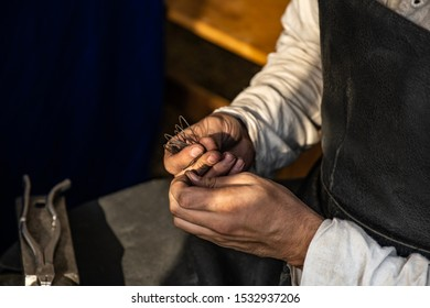 Hands of a craftsman. Blacksmith holds the wire with his hands. Create chain mail. Old crafts. Conducts a master class. Workshop. Dressed in an old outfit. Nearby are pliers for metal. Craft training.