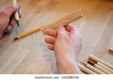Hands of the craftsman carve with a gouge. Wood carving. Wood carving set on a wooden table. Wood chisels selection. Wooden plate with inscription.