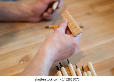 Hands of the craftsman carve with a gouge. Wood carving. Wood carving set on a wooden table. Wood chisels selection. Wooden plate with inscription. Rock.